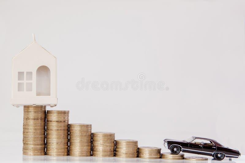 Um modelo preto de um carro e de uma casa com moedas sob a forma de um histograma em um fundo branco Conceito do empréstimo, econ foto de stock