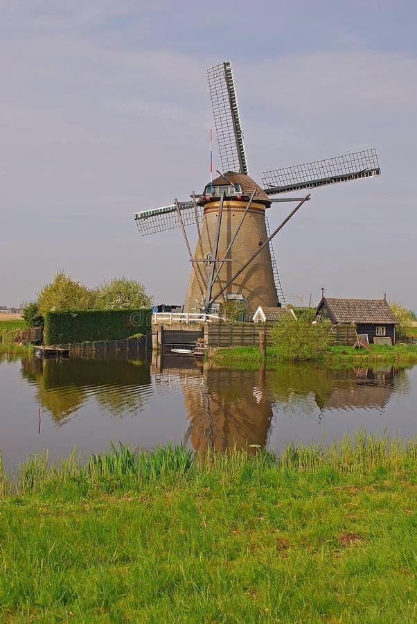 Um moinho de vento ao lado de uma casa no kinderdijk com reflexão bonita do tempo & da água foto de stock