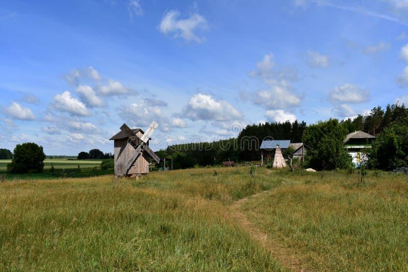 Um moinho de vento de madeira abandonado no campo verde vasto perto dos celeiros da floresta e outras construções estão em seguid foto de stock