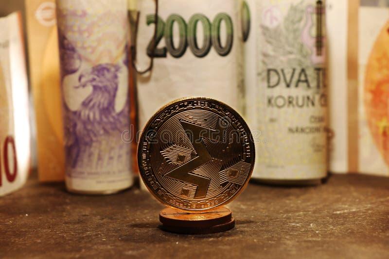 Um monero do ouro com dinheiro checo no fundo fotos de stock