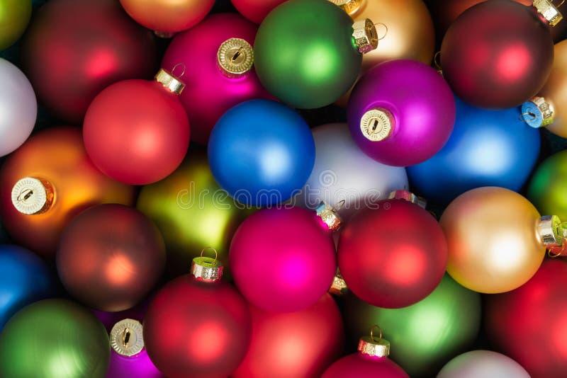 Um montão das quinquilharias coloridas do Natal que encontram-se no assoalho foto de stock