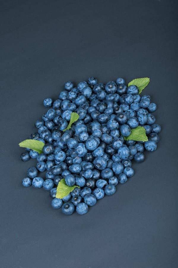Um montão de mirtilos doces e naturais com hortelã em uma obscuridade - fundo azul Ingredientes orgânicos para petiscos saudáveis fotografia de stock royalty free