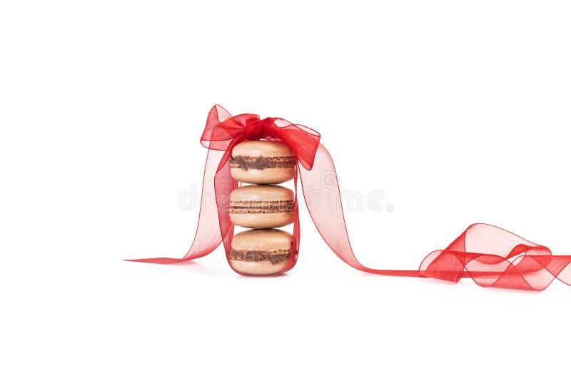 Um montão de três macarons com um laço vermelho fotos de stock