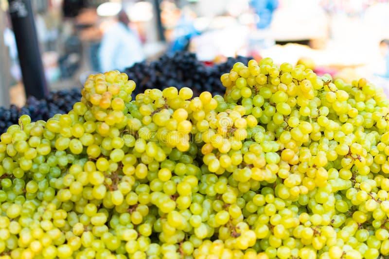 Um montão de uvas frescas verdes no fundo obscuro do mercado, Índia, Varanasi fotografia de stock royalty free