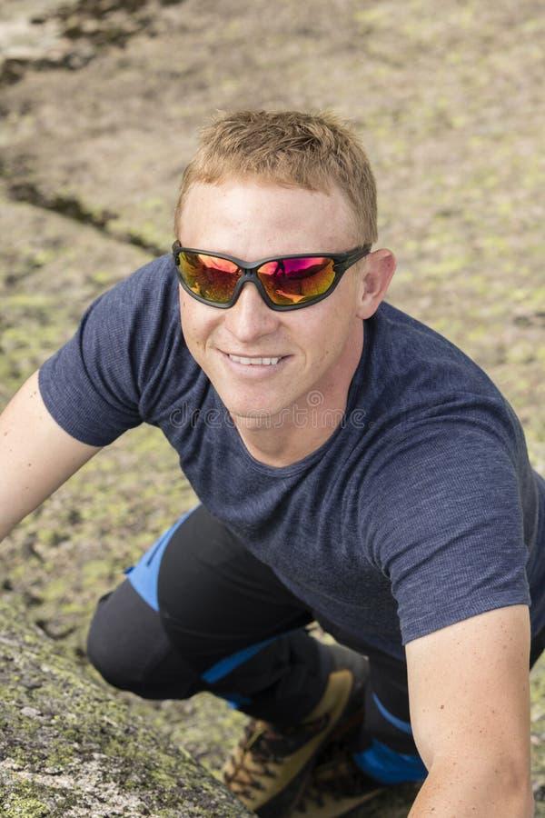 Um montanhista faz exercícios de escalada em uma rocha grande fotografia de stock royalty free