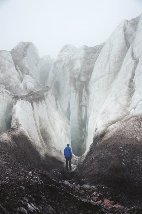 Um montanhista livre com um machado de gelo está no pé da grande geleira ao lado de uma quebra épico na névoa nas montanhas fotografia de stock royalty free