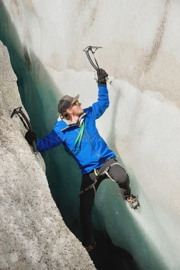 Um montanhista livre sem seguro com os dois machados de gelo aumenta de uma quebra na geleira Escalada livre sem cordas imagens de stock