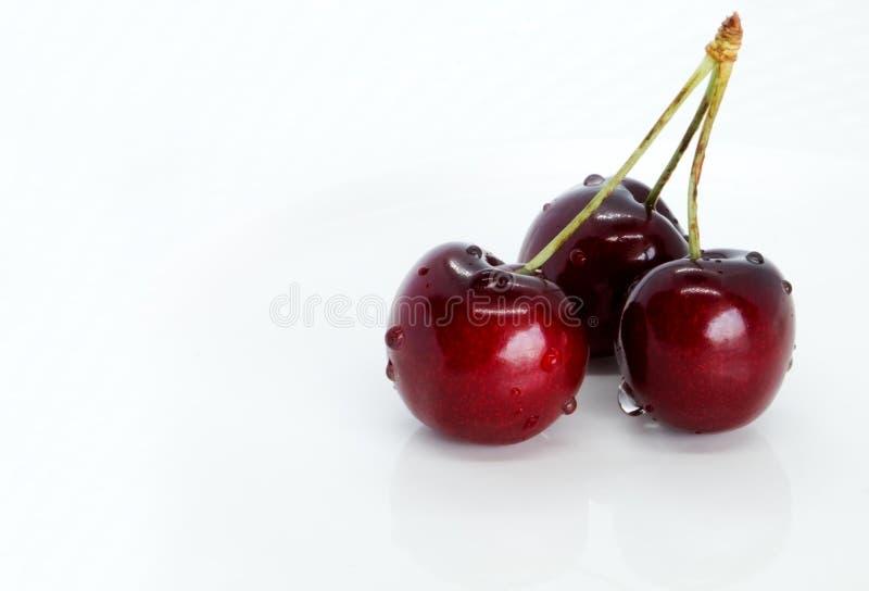 Um monte de cerejas doces numa placa branca foto de stock