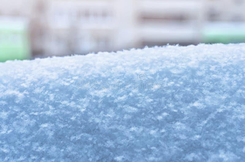 Um monte de neve com flocos de neve em um fundo borrado do prédio de apartamentos Estação do inverno, previsão de tempo, imagem d fotos de stock