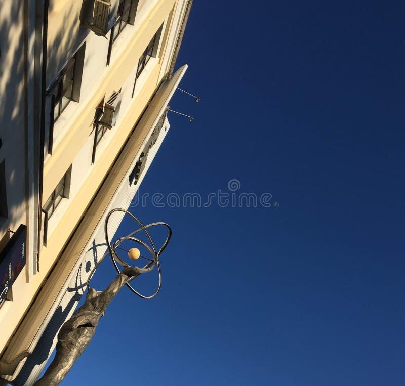 Um monumento com os homens que que guardam o átomo em um fundo do céu azul fotografia de stock
