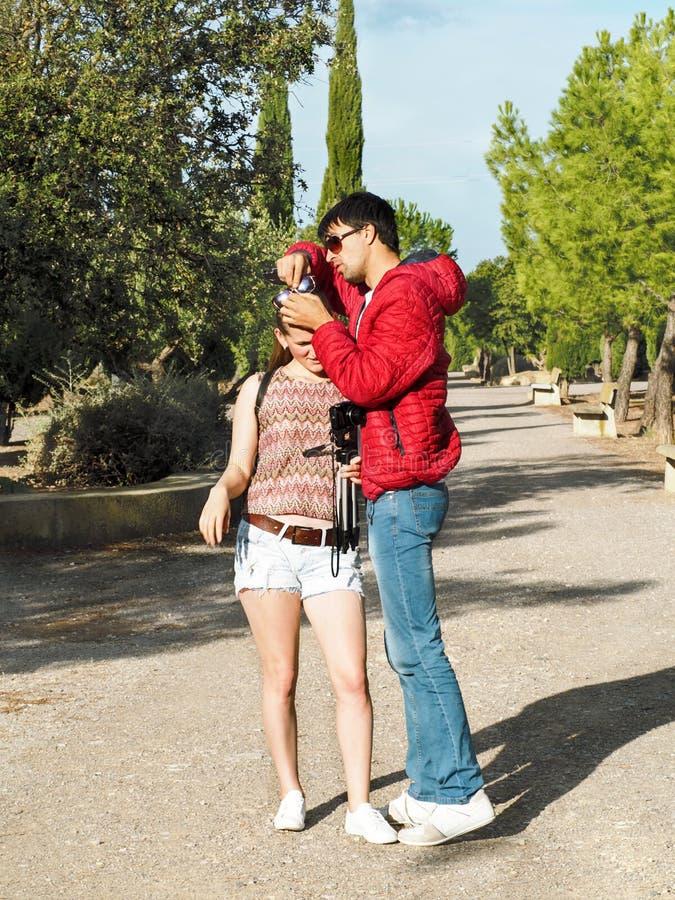 Um moreno alto decola os óculos de sol complicados no cabelo louro de uma jovem mulher com uma câmera imagem de stock royalty free