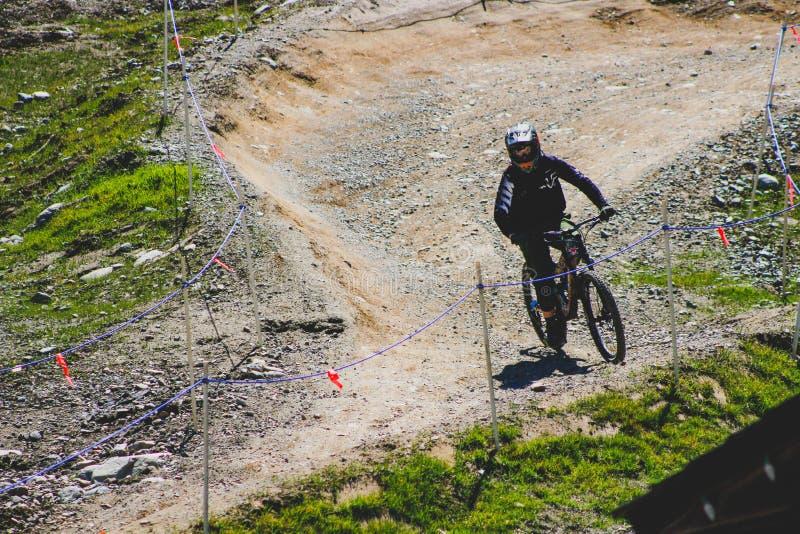 Um motociclista da montanha que vai abaixo da montanha do assobiador, Canadas a maioria de montanha icónica para esportes em decl imagem de stock royalty free