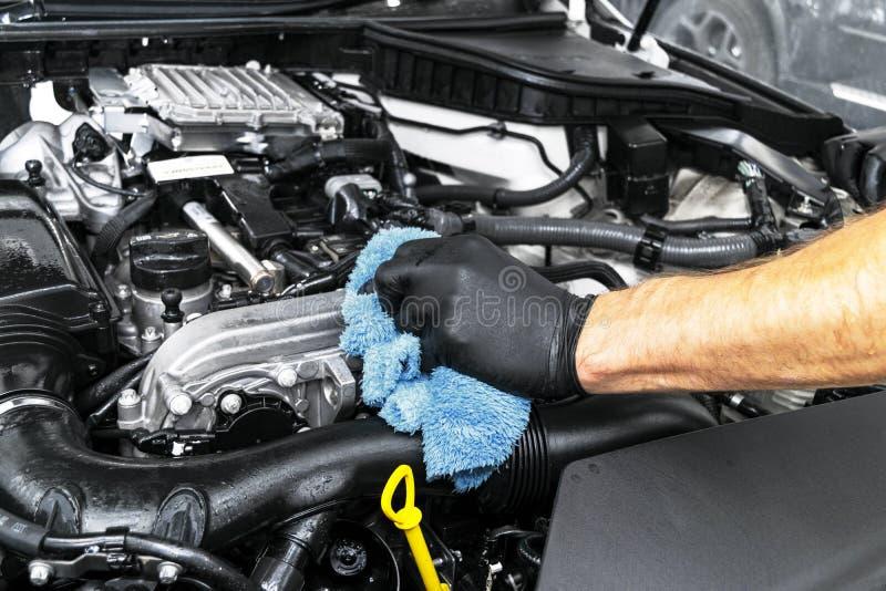 Um motor de automóveis de limpeza do homem com pano do microfiber Conceito de detalhe ou valeting do carro Foco seletivo Detalhe  fotos de stock