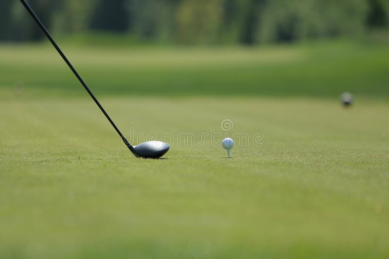 Um motorista do golfe com bola em um T no campo de golfe foto de stock