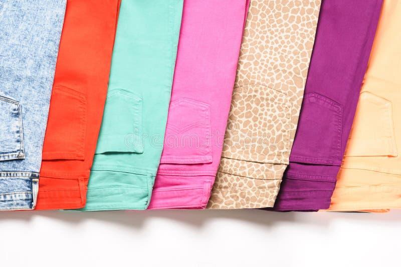 Um número de calças de brim coloridas no fundo branco fotos de stock royalty free