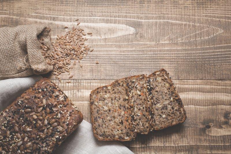 Um naco do pão de centeio inteiro rústico fresco da refeição, cortado em uma placa de madeira, fundo rural do alimento imagem de stock