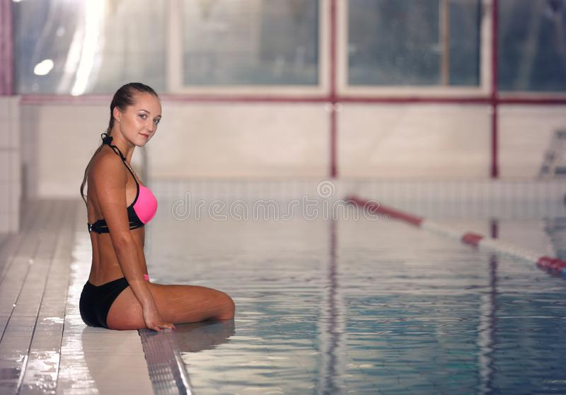 Um nadador fêmea na piscina do esporte interno menina no treinamento cor-de-rosa do sweimsuit imagem de stock