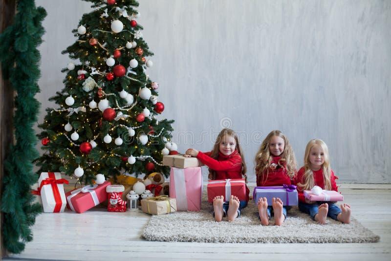 Um Natal aberto de três louros das meninas apresenta a árvore de Natal o ano novo imagens de stock