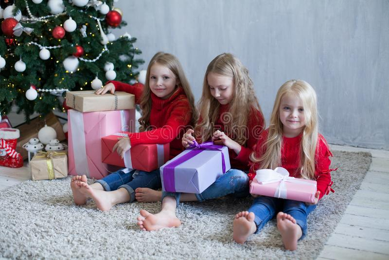 Um Natal aberto de três louros das meninas apresenta a árvore de Natal o ano novo imagem de stock royalty free
