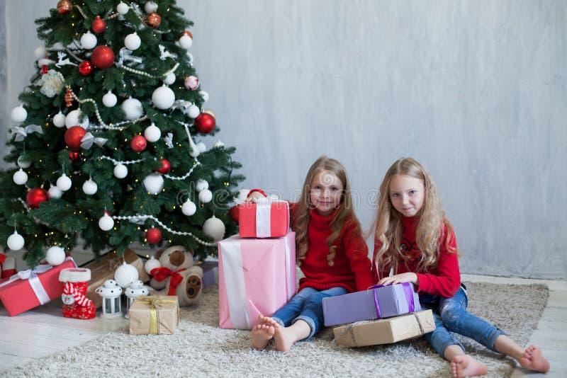 Um Natal louro de duas meninas das irmãs das amigas apresenta a árvore do ano novo imagem de stock royalty free