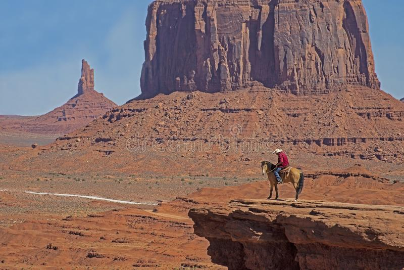 Um nativo americano anda seu cavalo no vale do monumento fotografia de stock