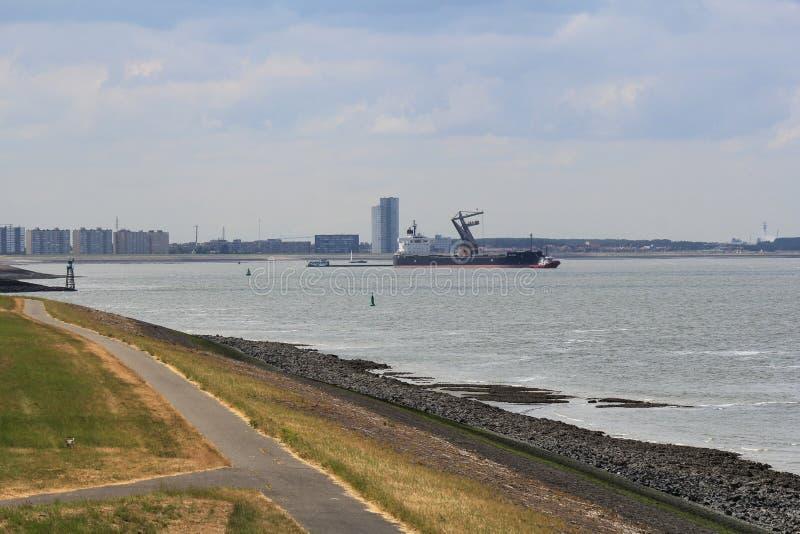 Um navio é descarregado no mar com a skyline de terneuzen no fundo em holland na mola foto de stock