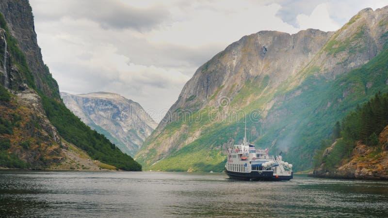 Um navio de cruzeiros pequeno com turistas começa uma viagem ao fiorde em Noruega imagens de stock