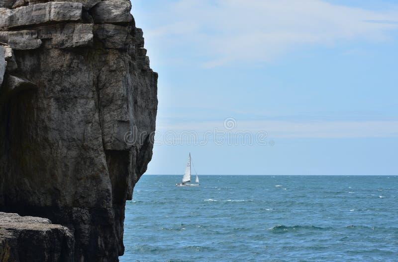 Um navio de navigação aparece atrás de um litoral rochoso imagens de stock