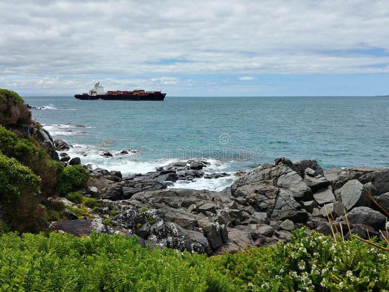 Um navio de recipiente está saindo do porto do blefe, Nova Zelândia foto de stock royalty free
