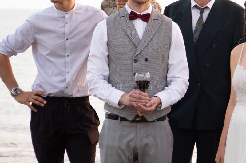 Um noivo feliz em um terno cinzento da forma está guardando um vidro do vinho tinto fotografia de stock