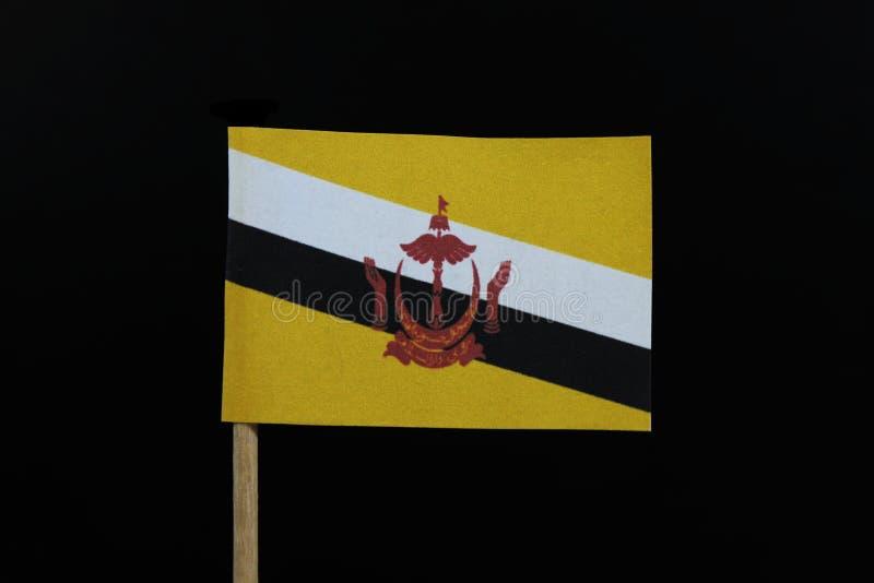 Um oficial e uma bandeira original de Brunei Darussalam no palito no fundo preto Uma crista vermelha centrada de Brunei Darussala imagem de stock