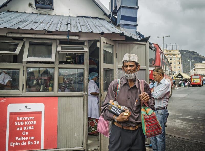 Um oldman está vendendo alguns bens na estação de ônibus fotografia de stock royalty free