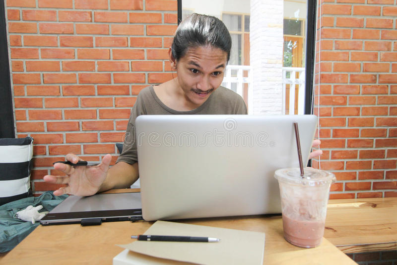 Um olhar do homem ao laptop surpreendido, homem asiático chocado com h fotos de stock