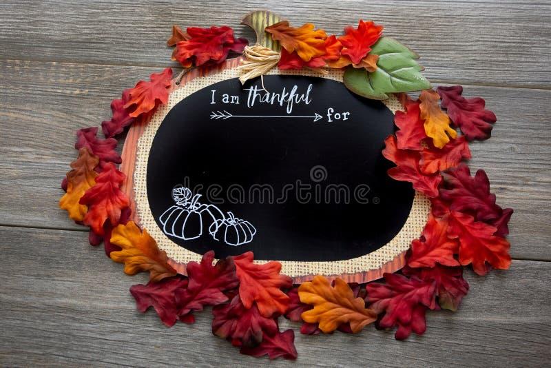 Um outono, queda inspirou-me é grato para o fundo cercado pelas folhas da queda em uma tabela de madeira Aperfeiçoe para um messa fotografia de stock