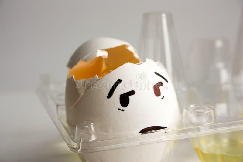Um ovo com uma cara Conceito da dor de cabeça hangover fotos de stock