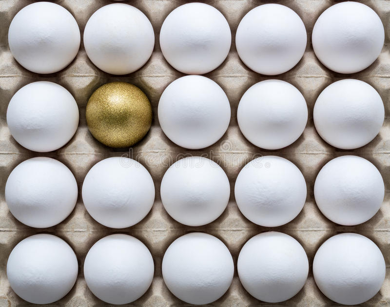 Um ovo dourado entre os ovos brancos em uma caixa de ovo da caixa fotografia de stock