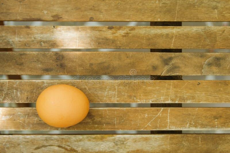 Um ovo na tabela de madeira fotografia de stock