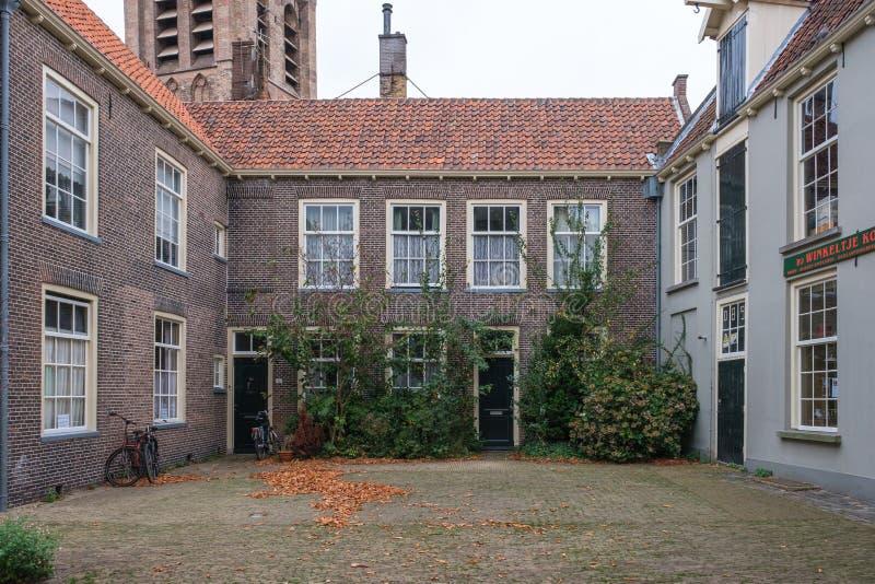 Um pátio bonito pequeno com as casas históricas na louça de Delft, Países Baixos foto de stock