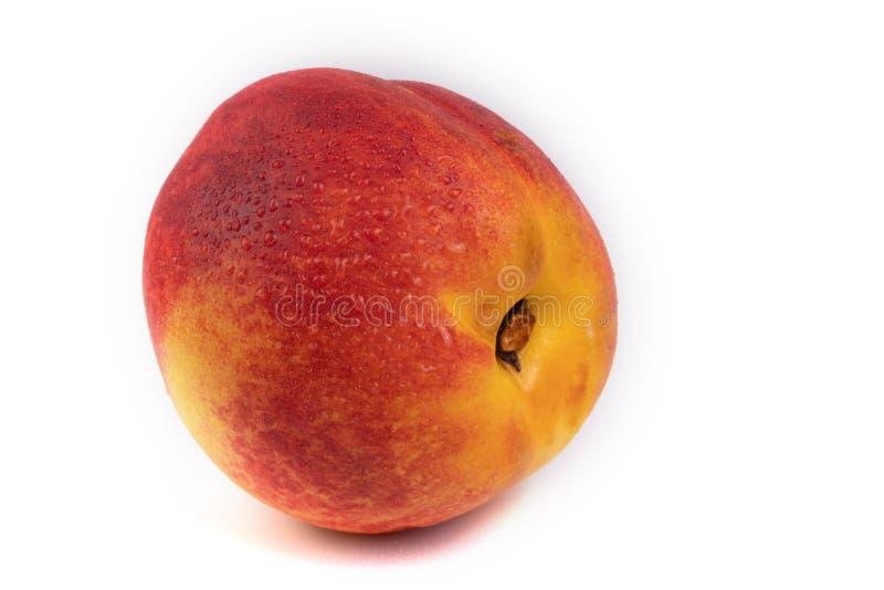 Um pêssego laranja e vermelho espalhado com gotas minúsculas de água sobre o lado fotos de stock