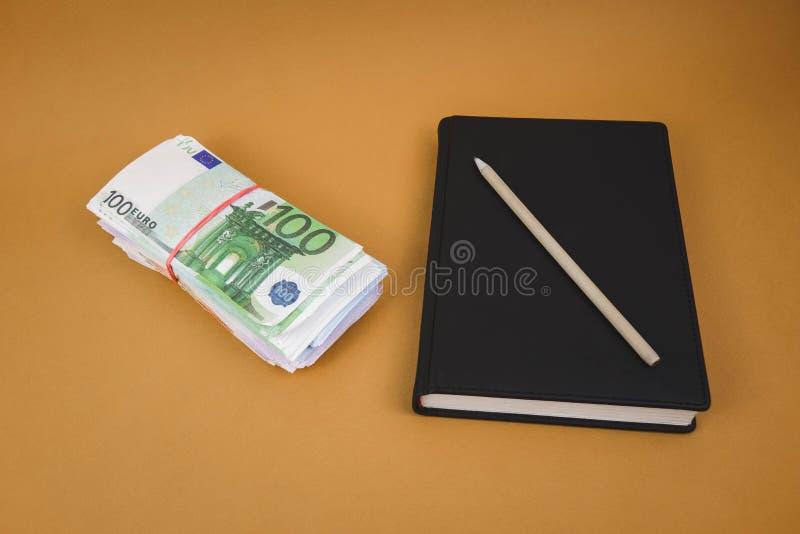 um pacote de dinheiro um caderno preto em um fundo alaranjado liso fotos de stock royalty free
