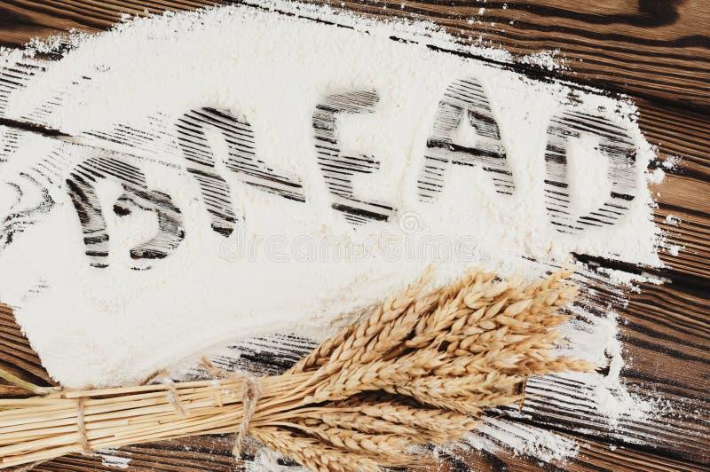 Um pacote de trigo e papoila e a escrita exprimem PÃO na farinha em pranchas de madeira velhas fotos de stock