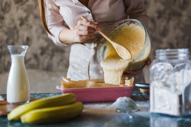 Um padeiro da jovem mulher está derramando a massa em um prato do cozimento foto de stock