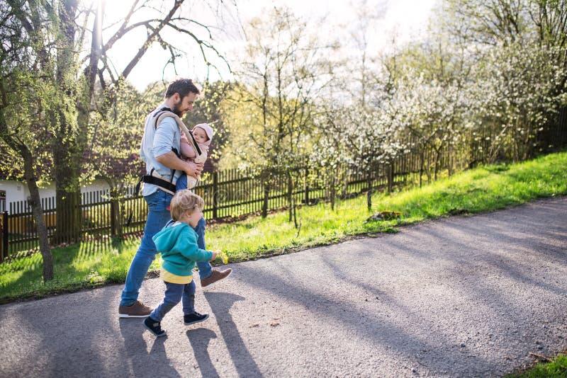 Um pai com suas crianças da criança fora em uma caminhada da mola fotografia de stock