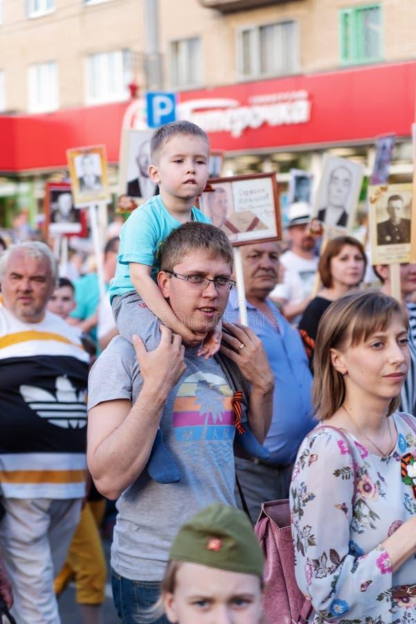 Um pai novo com um filho em seus ombros, participantes no regimento imortal da ação imagens de stock