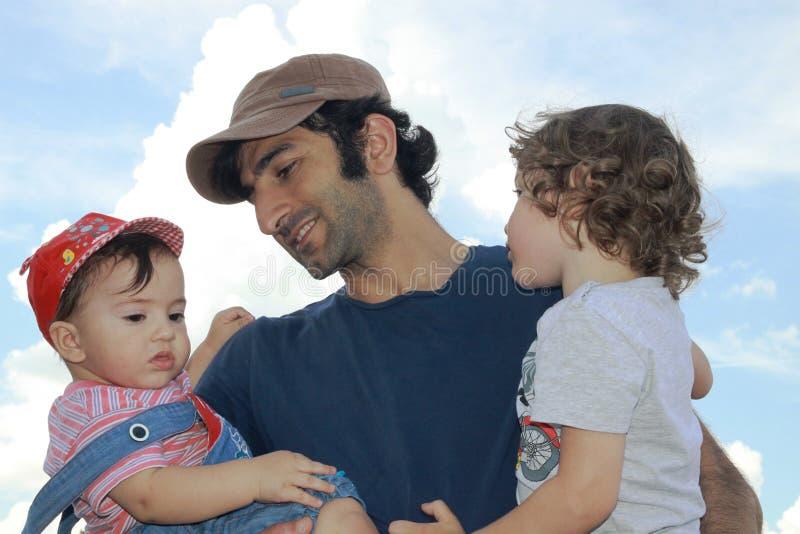 Um pai novo com os dois filhos novos em seus braços sob um céu azul do verão imagens de stock