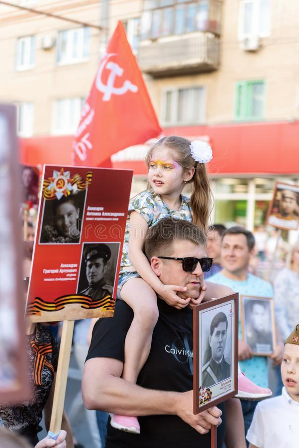 Um pai novo com uma filha em seus ombros, participantes no regimento imortal da ação fotografia de stock
