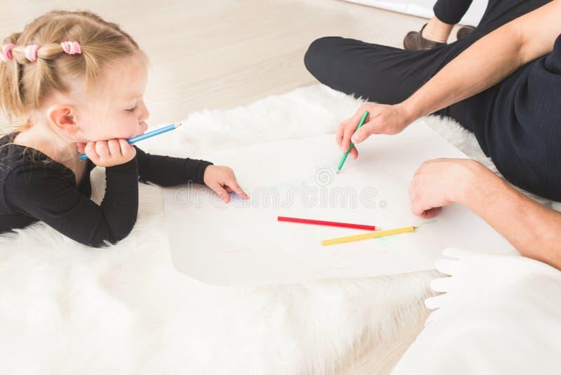 Um pai novo e sua mentira da filha no assoalho e tração com lápis coloridos imagem de stock
