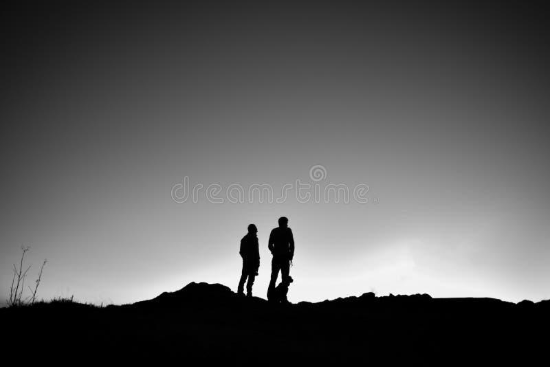 Um paizinho com sua posição do filho com seu cão em um cume que olha a elevação do sol foto de stock royalty free