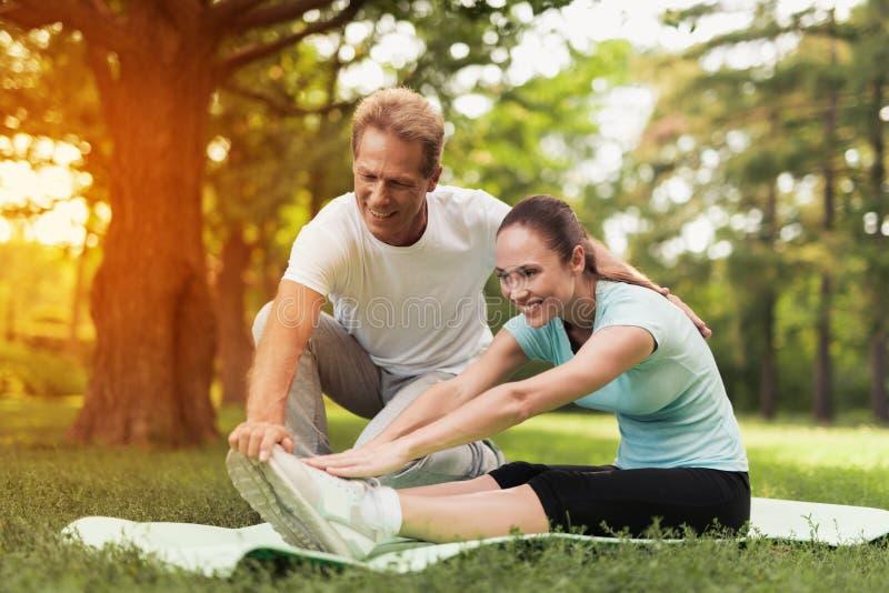 Um par é contratado nos esportes em um parque morno do verão Um homem ajuda uma mulher a esticar imagem de stock