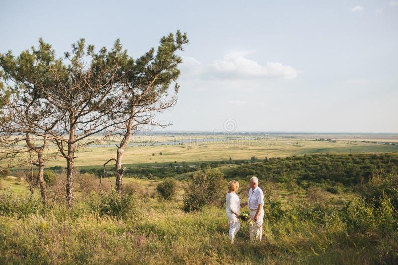 Um par adultos superiores no vestido de linho branco estão estando fora, nas mãos um ramalhete das flores, três fotografia de stock royalty free